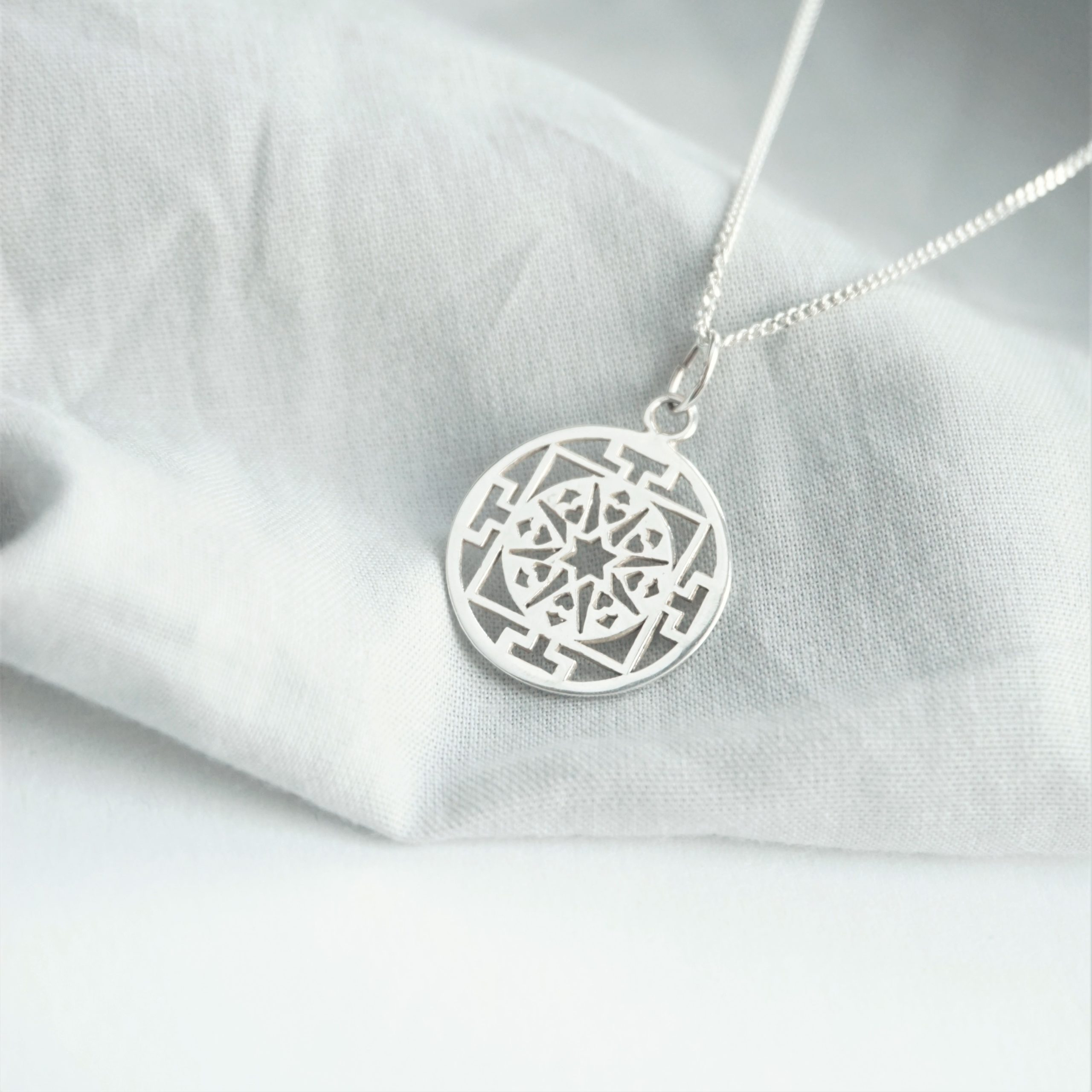 sterling silver necklace with circular design charm