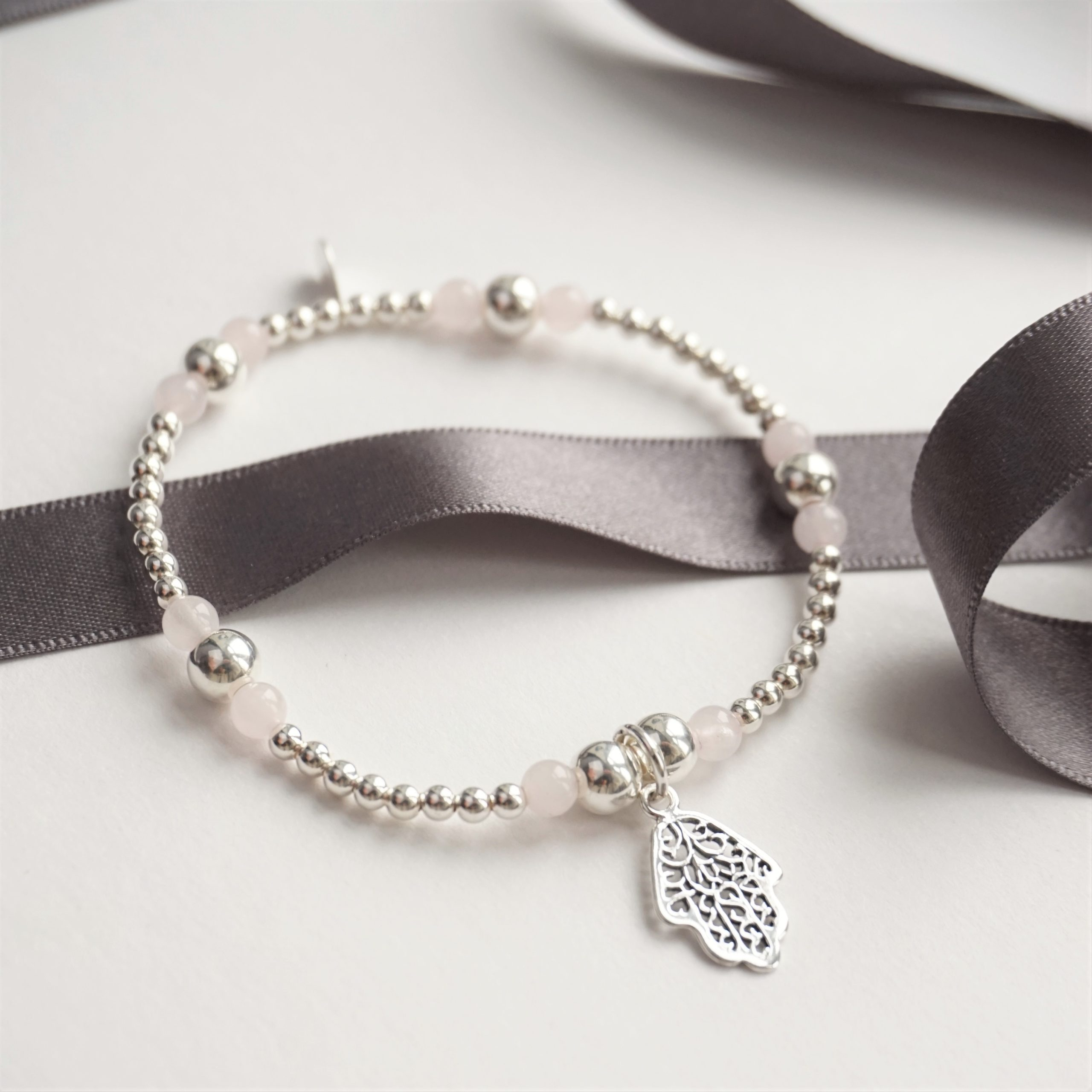 sterling silver bracelet with rose quartz beads and hamsa hand charm