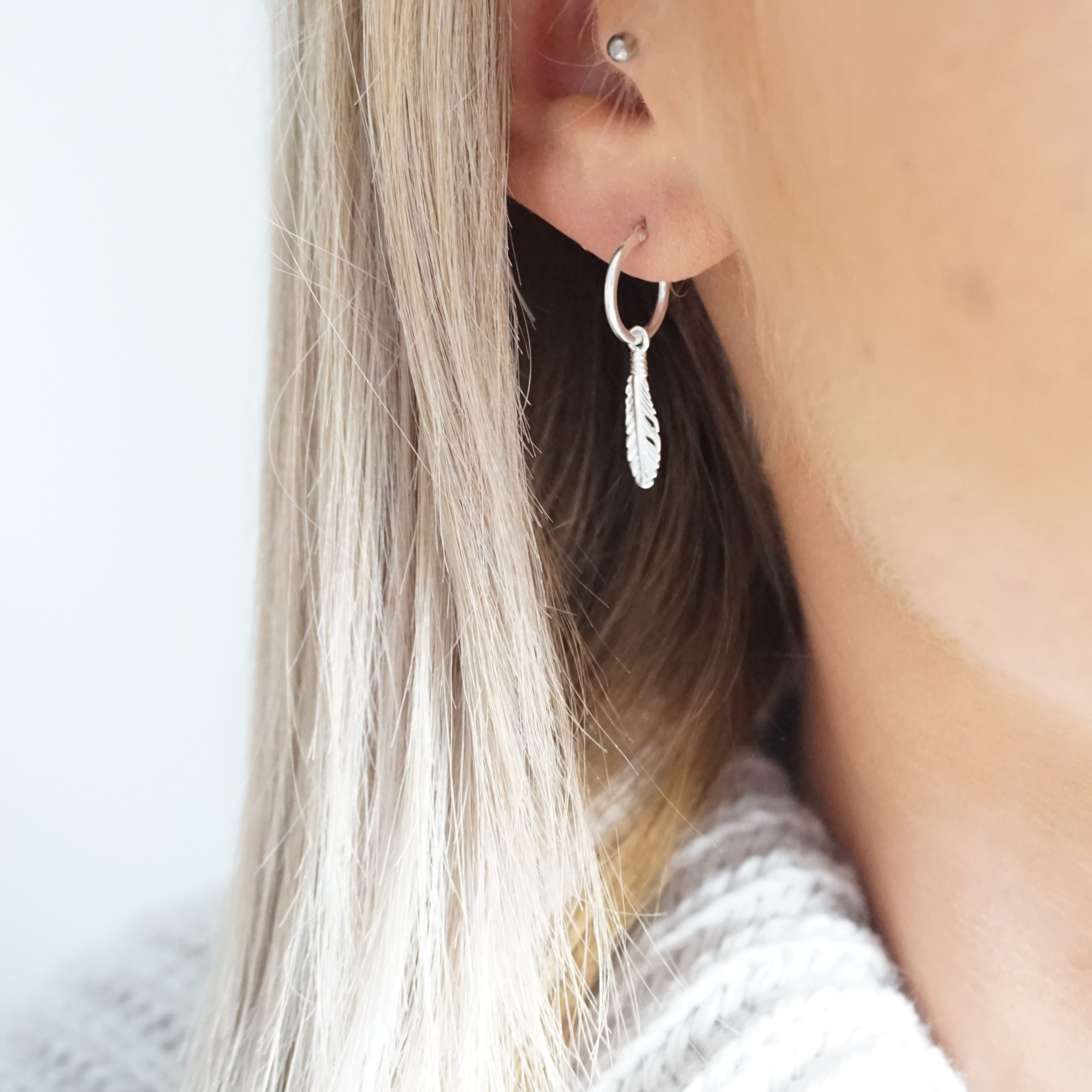 Sterling silver hoop earrings with feather charms