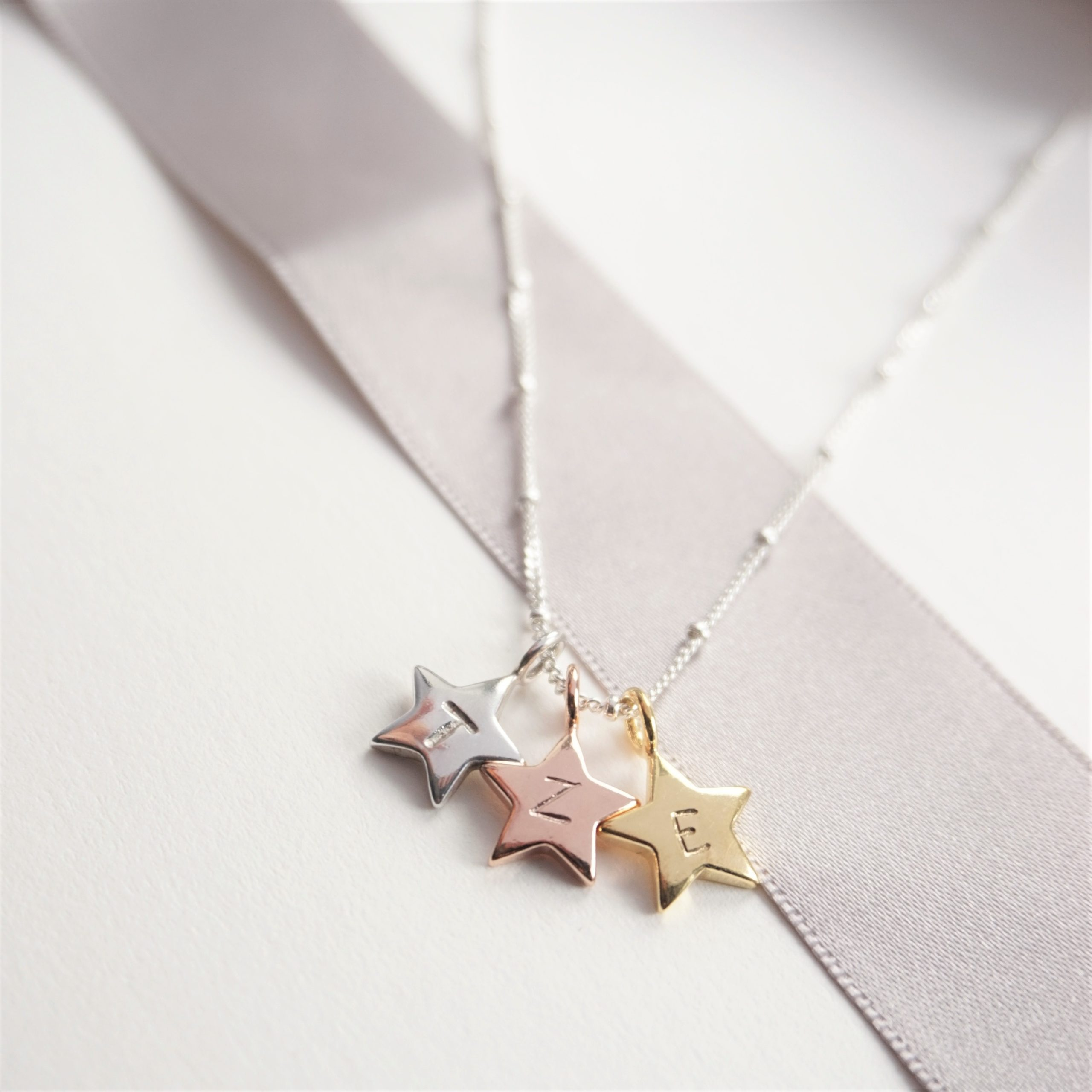 Sterling silver necklace with gold rose gold and silver initial stamped star charms